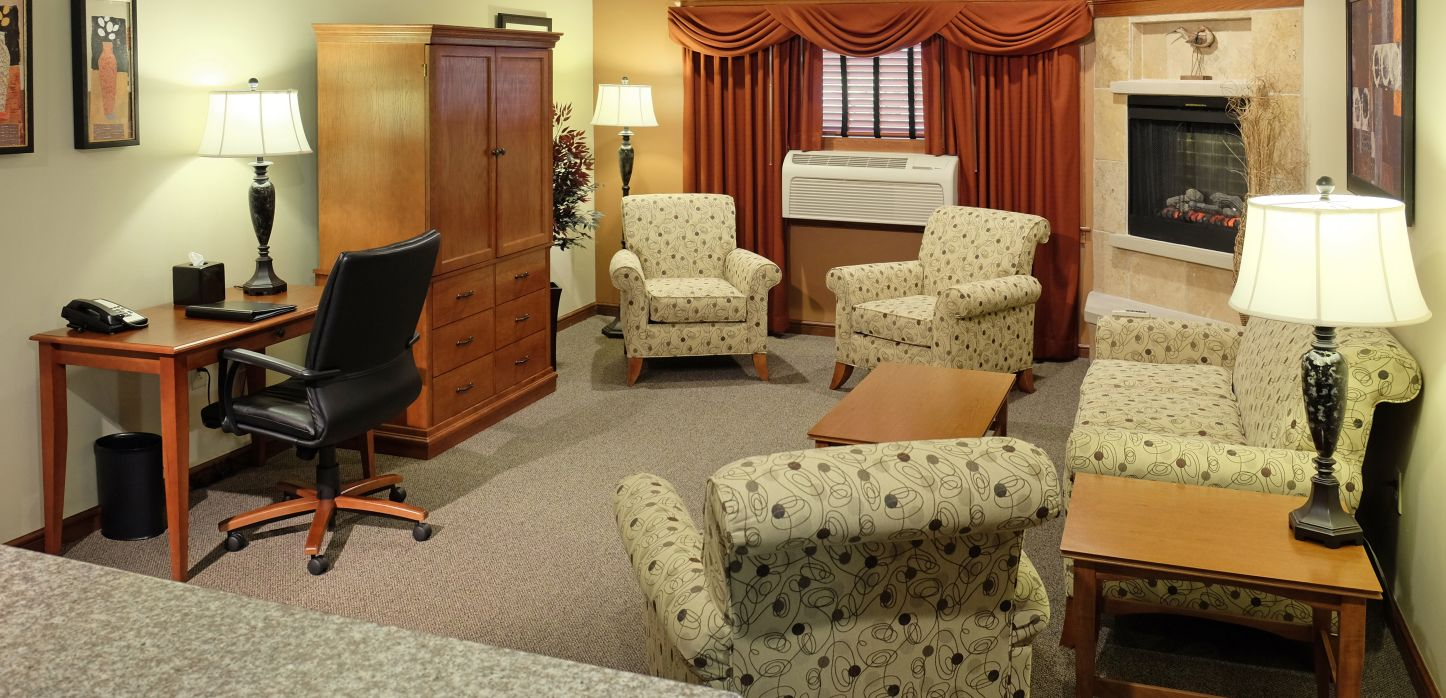 bedroom suite with 4 chairs and fireplace