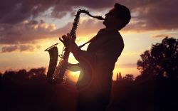 guy playing on saxophone against sunset